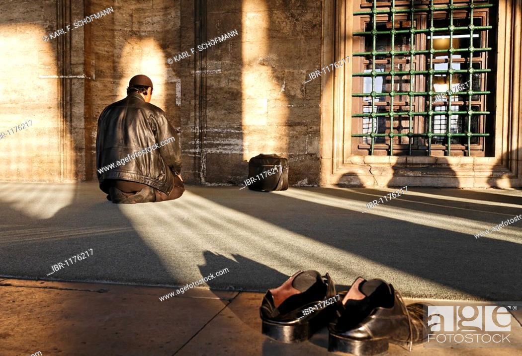 Muslim man praying in front of a prayer niche, shoes taken