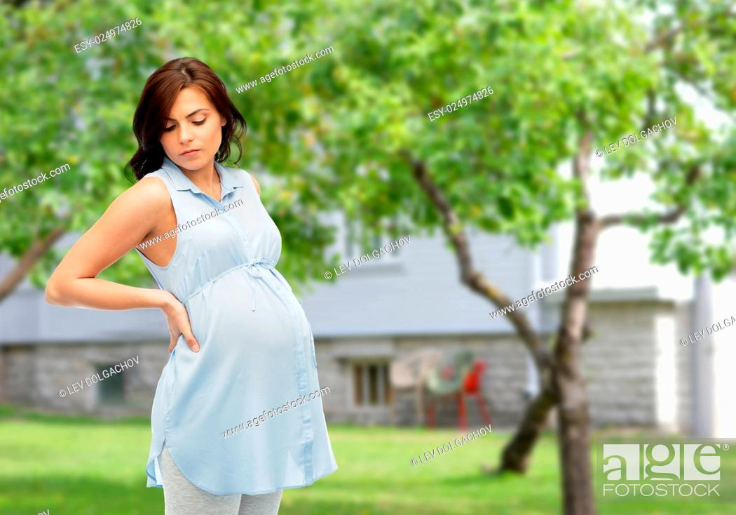 Stock Photo: pregnancy, health, people and expectation concept - pregnant woman touching her back and suffering from backache over summer garden and house background.