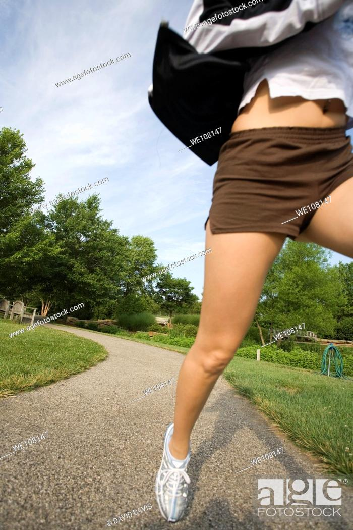 Stock Photo: Young woman in early 20s jogging in park.