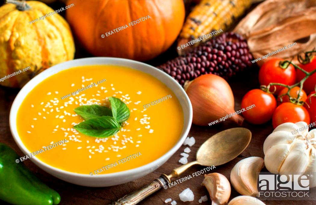 Stock Photo: Fresh pumpkin soup with a spoon and vegetables on a wooden table.