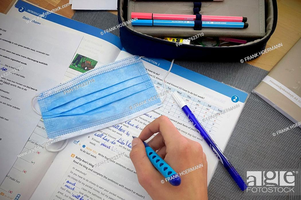 Stock Photo: Theme picture school in times of the coronavirus pandemic, mask requirement. A student is doing his homework. A disposable mask is on his handle.