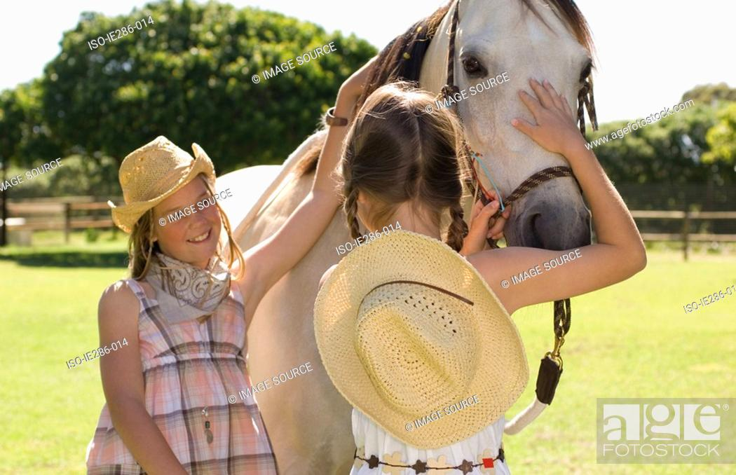 Stock Photo: Two girls stroking a horse.