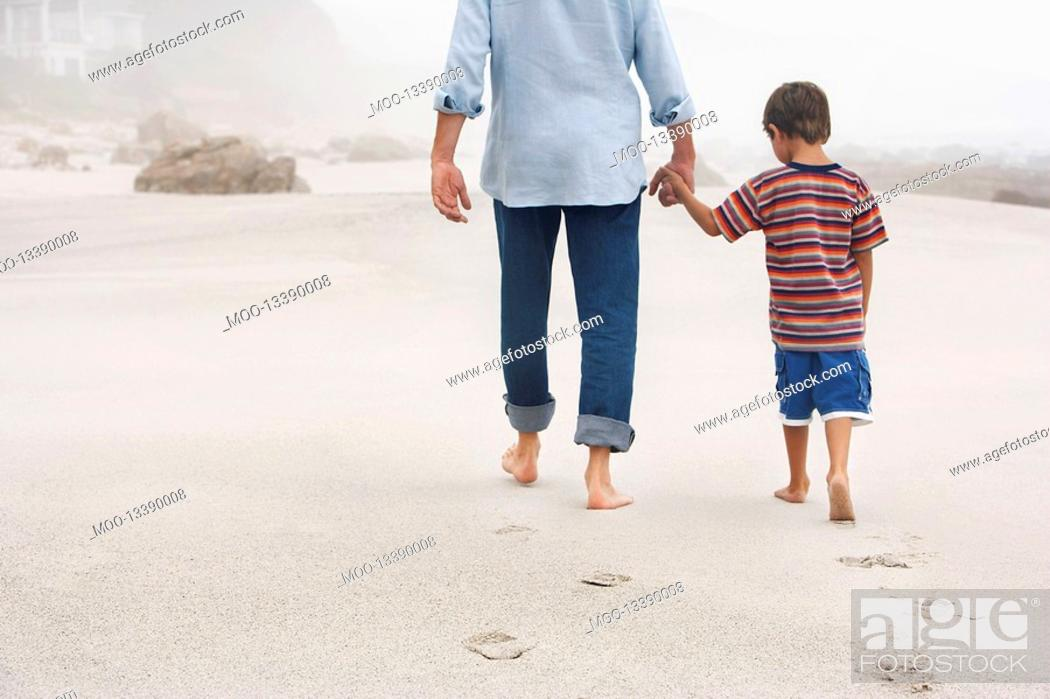 Stock Photo: Father and son 5-6 holding hands walking on beach back view.
