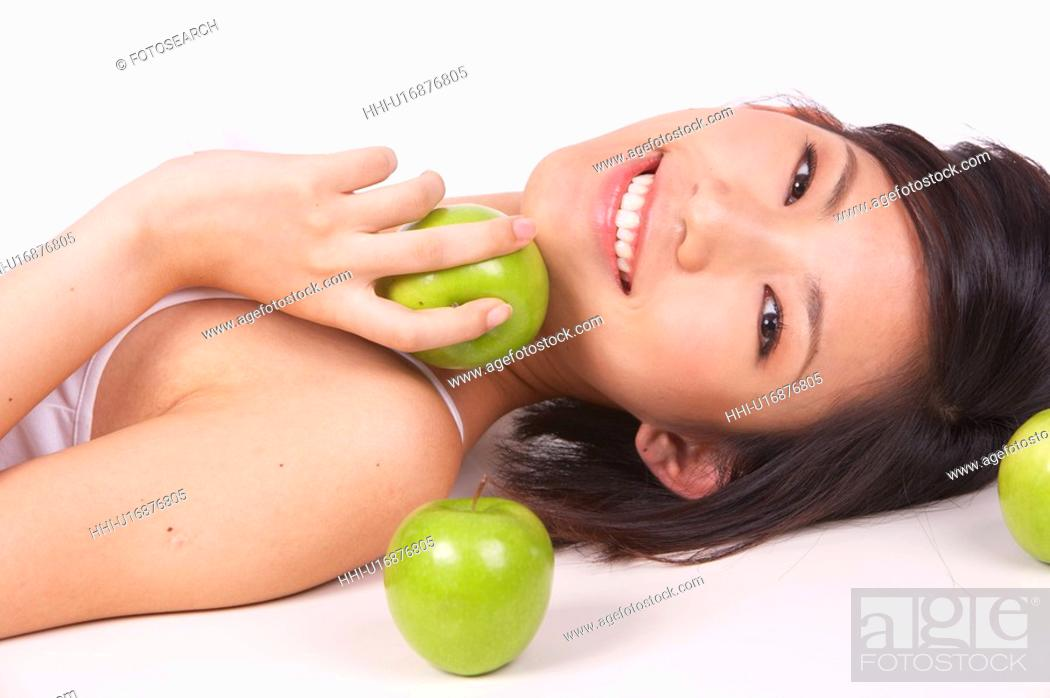 Stock Photo: Portrait of Natural Young girl lying on Floor, Holding Apple.