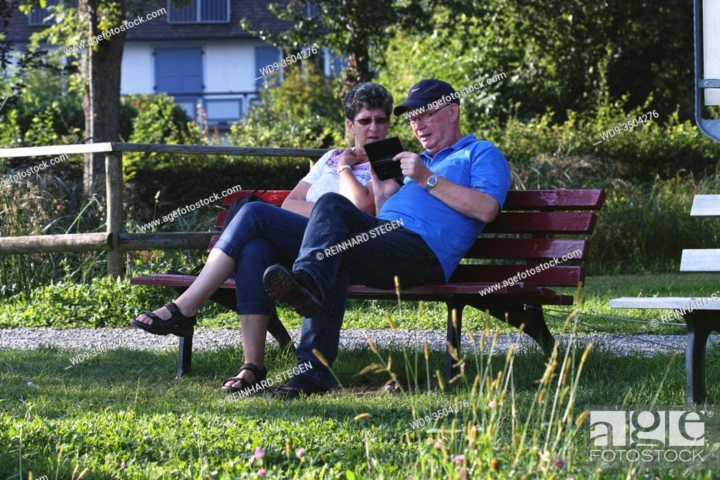 Stock Photo: older couple, on bench, inspecting pics, images, on smartphone.
