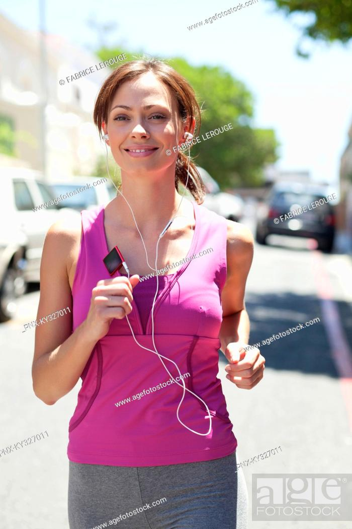 Stock Photo: Beautiful young woman listening to mp3 player while jogging.