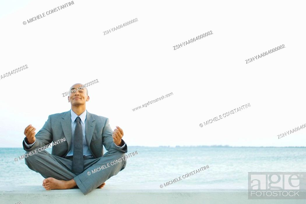 Stock Photo: Businessman sitting in lotus position at the beach, eyes closed.