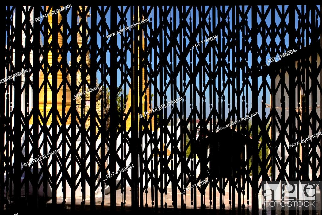 Stock Photo: A Buddhist temple viewed from behind metal shutters, Inle Lake, Burma.
