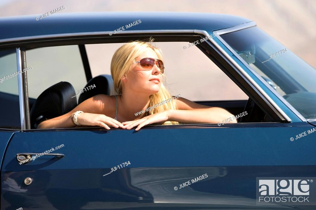 Stock Photo: Young woman in sunglasses in car, looking out window, side view.
