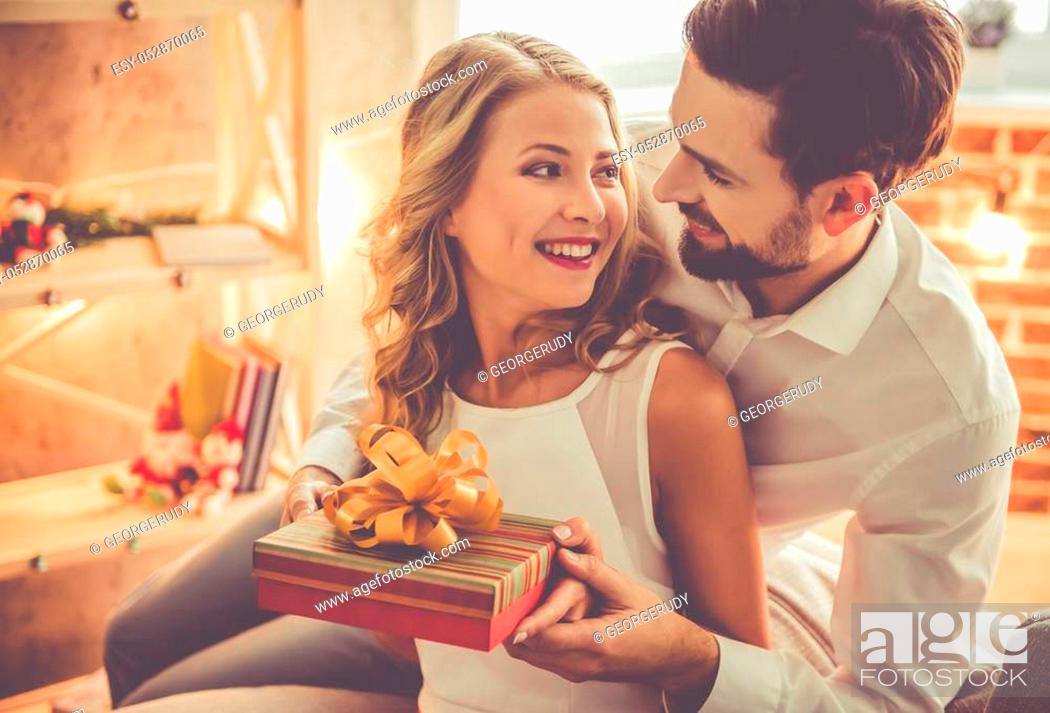 Photo de stock: Beautiful young couple is celebrating at home. Handsome man is giving his girlfriend a gift box.