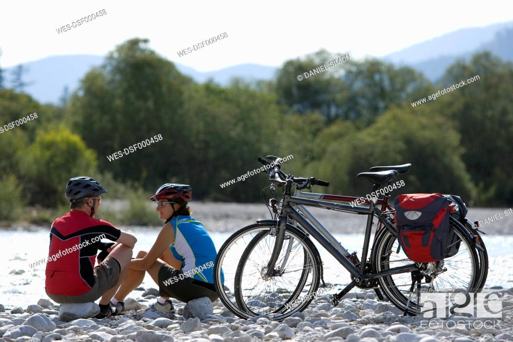 Stock Photo: Germany, Bavaria, Man and woman sitting by bicycle.