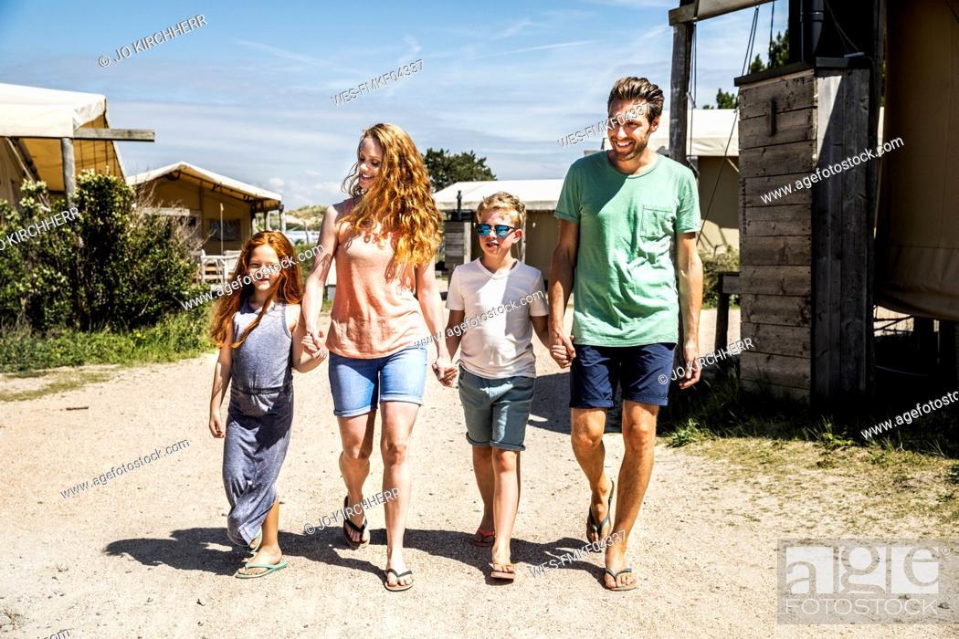 Photo de stock: Netherlands, Zandvoort, happy family walking on campsite.
