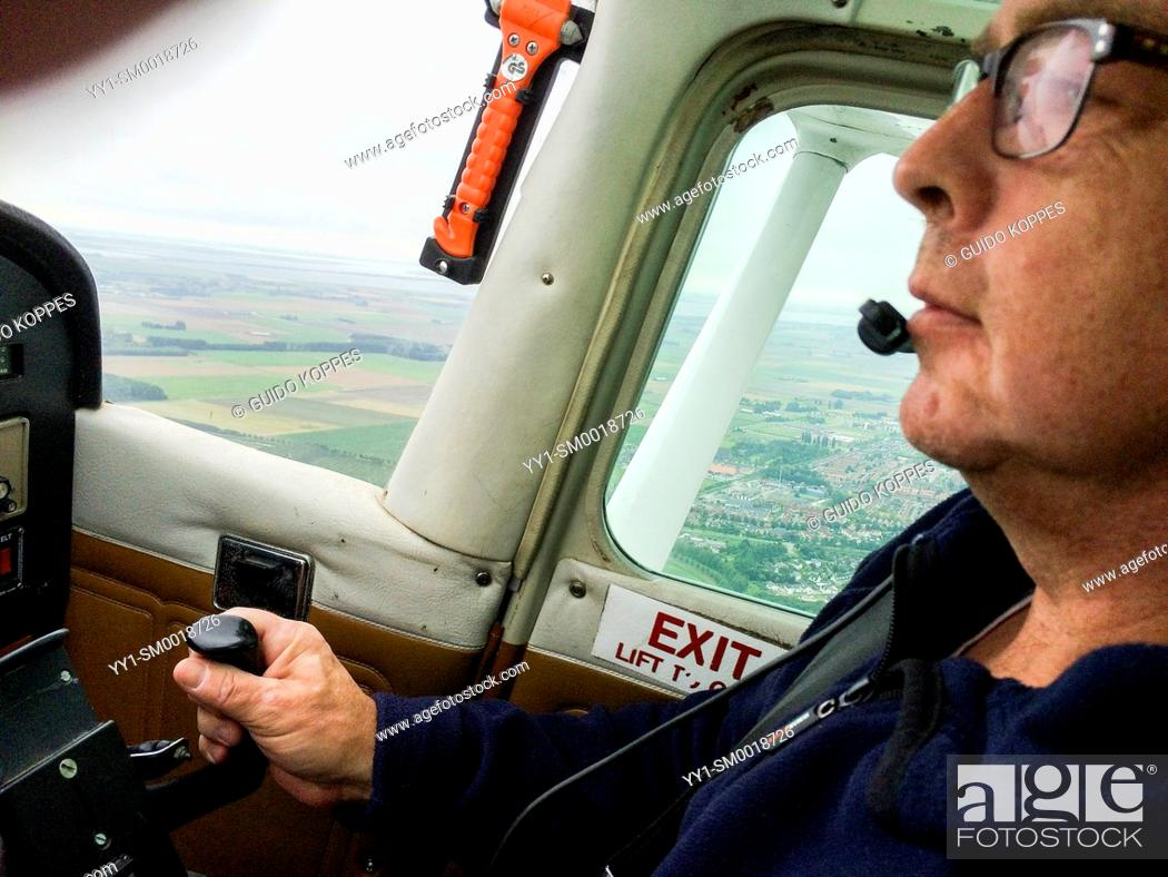 Photo de stock: Southern Airspace, Netherlands. Mature adult male flying single prop Cessna airplane.