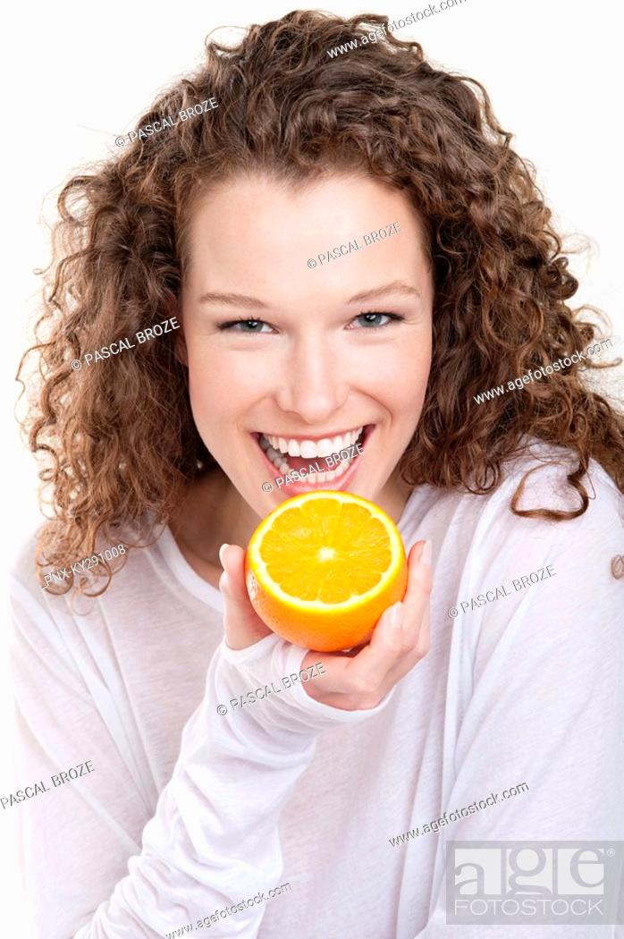 Stock Photo: Portrait of a woman holding a half of an orange and laughing.
