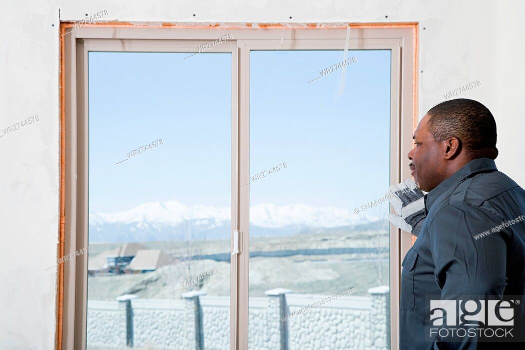 Stock Photo: A builder looking out of a patio door.