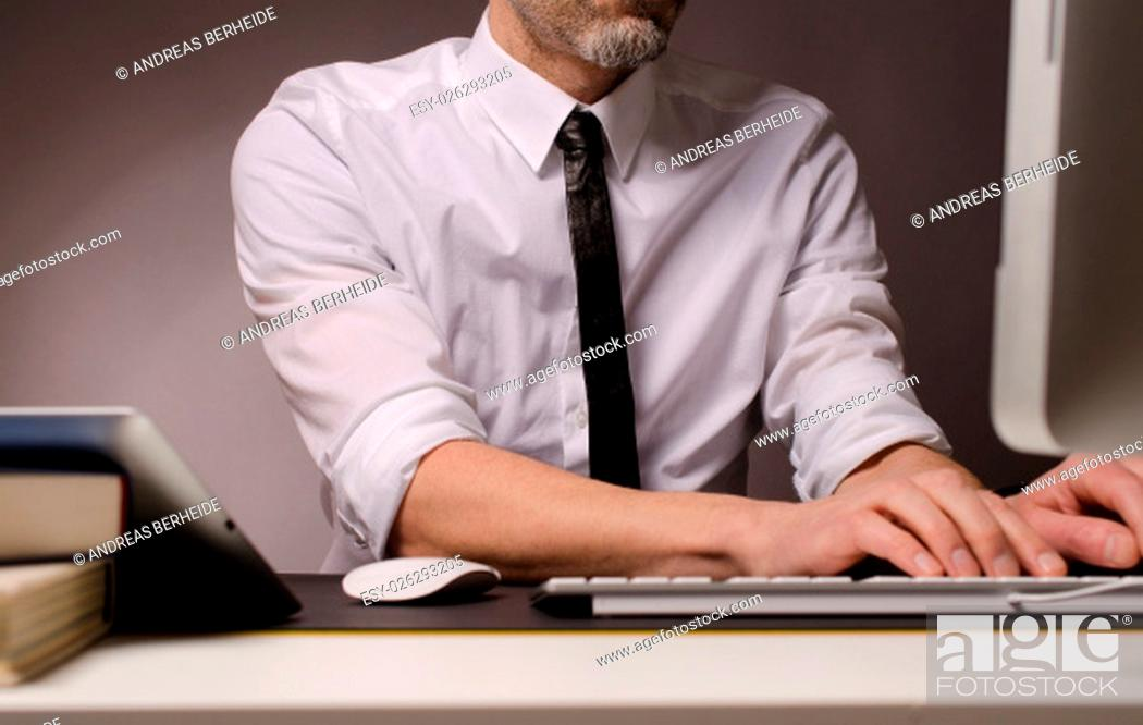 Stock Photo: Business man with different devices working on a computer.