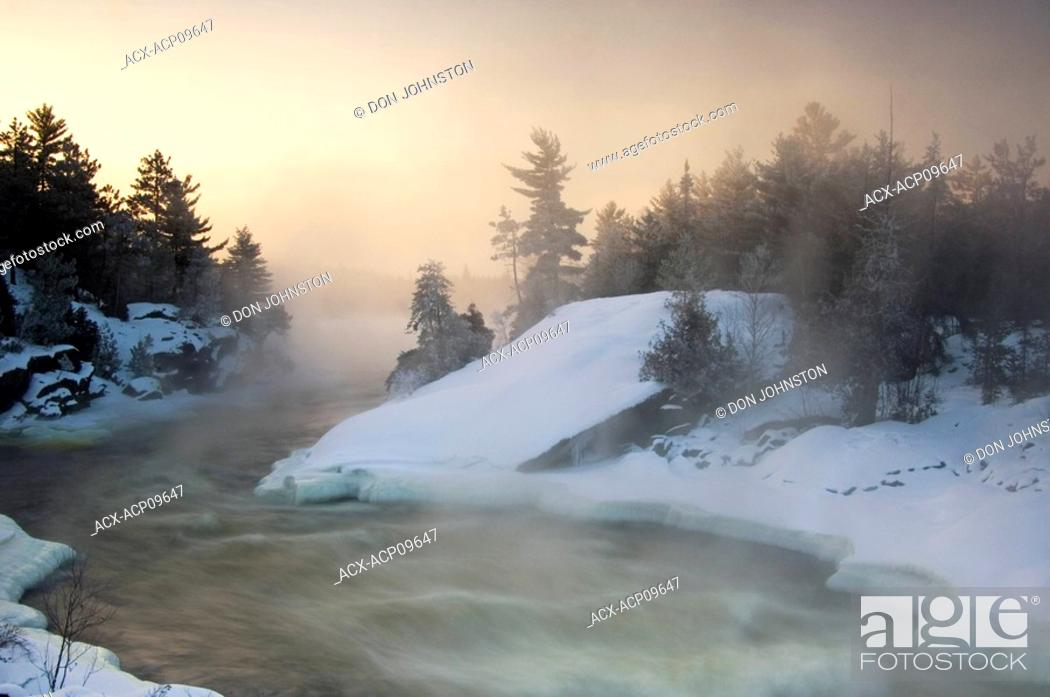 Stock Photo: Tree silhouettes and rising mists near rapids of Wahnapitei River at sunrise, Wanup, Ontario, Canada.