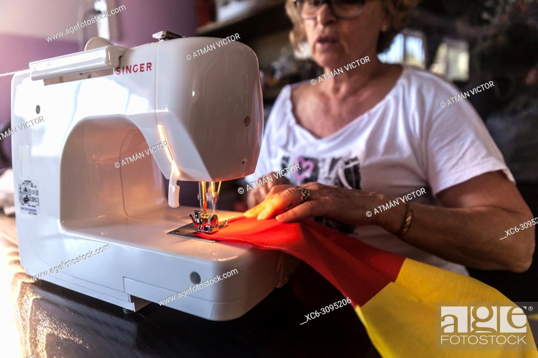 Stock Photo: adult woman sewing the spanish flag with a SINGER brand sewing machine. Tenerife island.