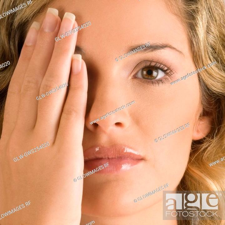 Stock Photo: Close-up of a young woman covering her one eye.
