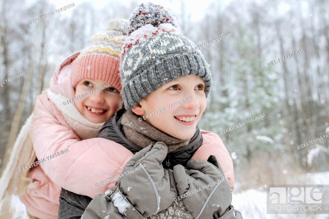 Stock Photo: Portait of boy giving his little sister a piggyback ride in winter forest.