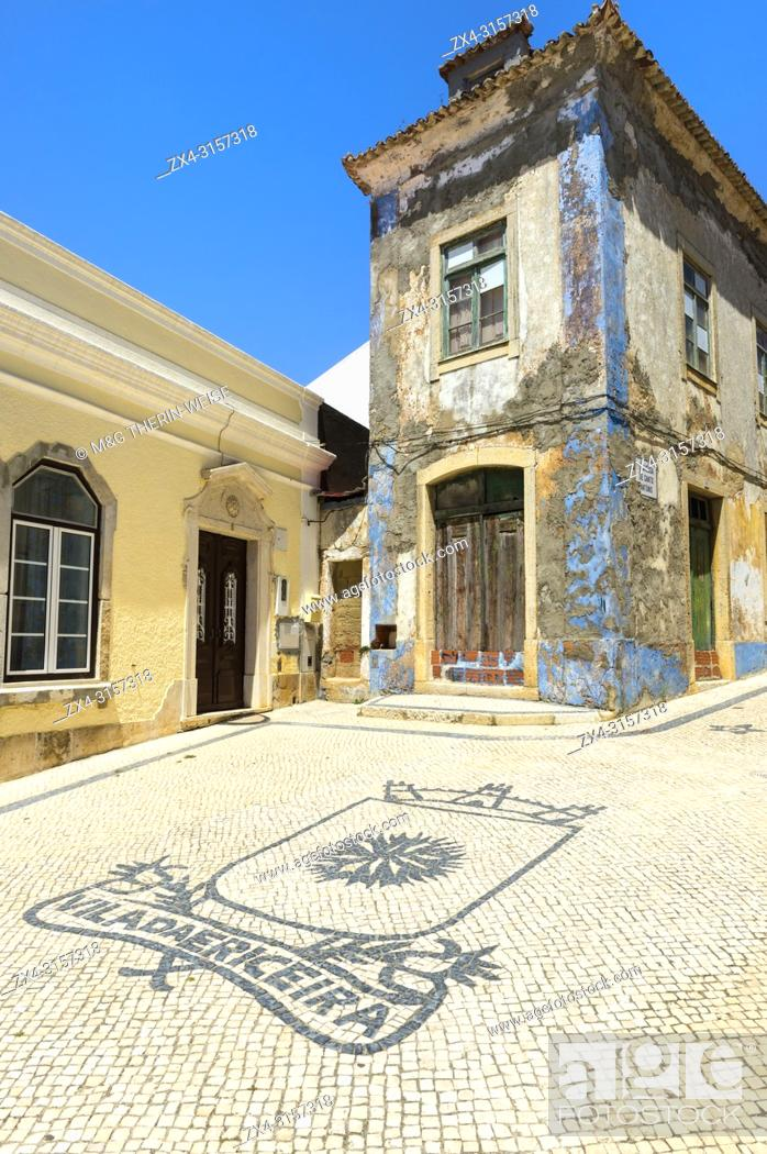 Photo de stock: Coats of arm of Ericeira city on cobblestones in front of an old house, Ericeira, Lisbon Coast, Portugal.