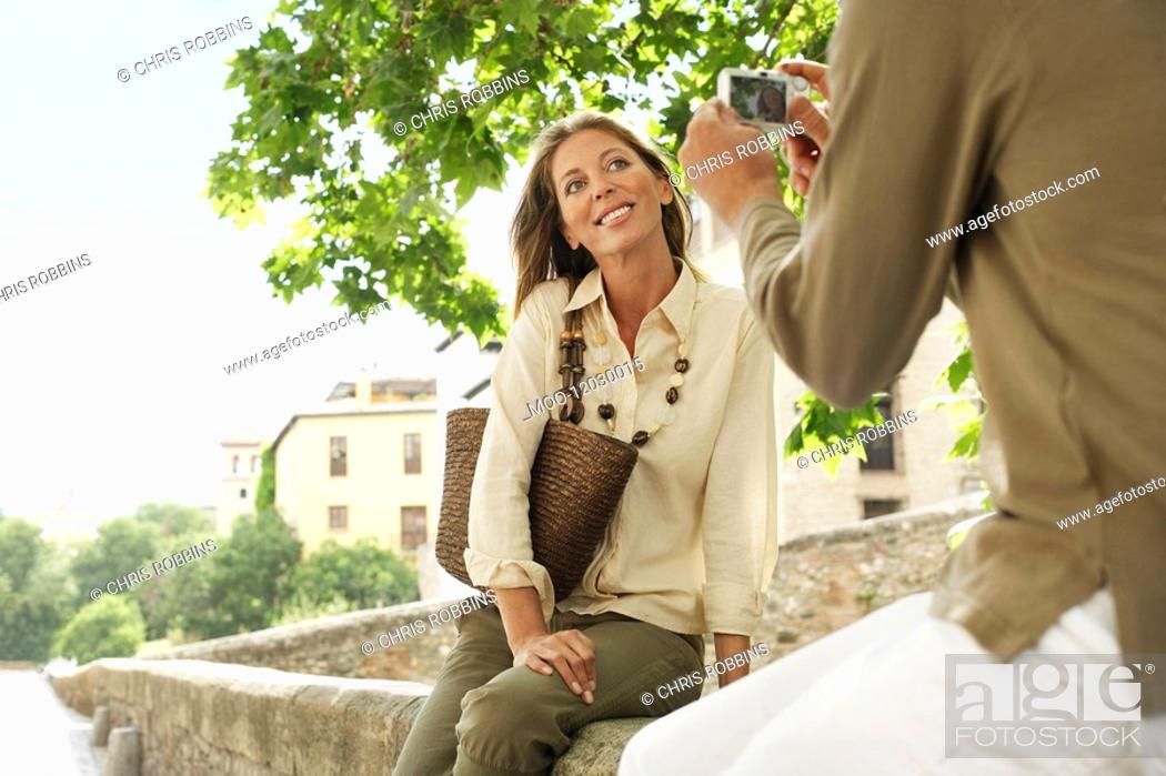 Stock Photo: Man taking picture of partner on wall in Granada Spain back view low angle view.