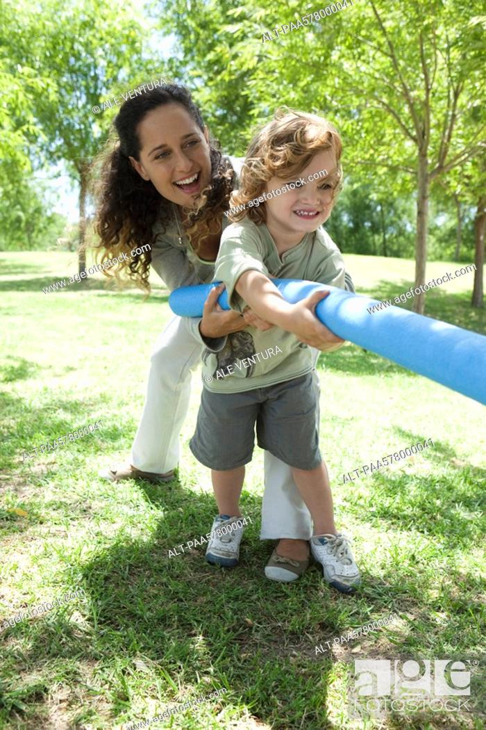 Stock Photo: Mother and young son playing tug-of-war.