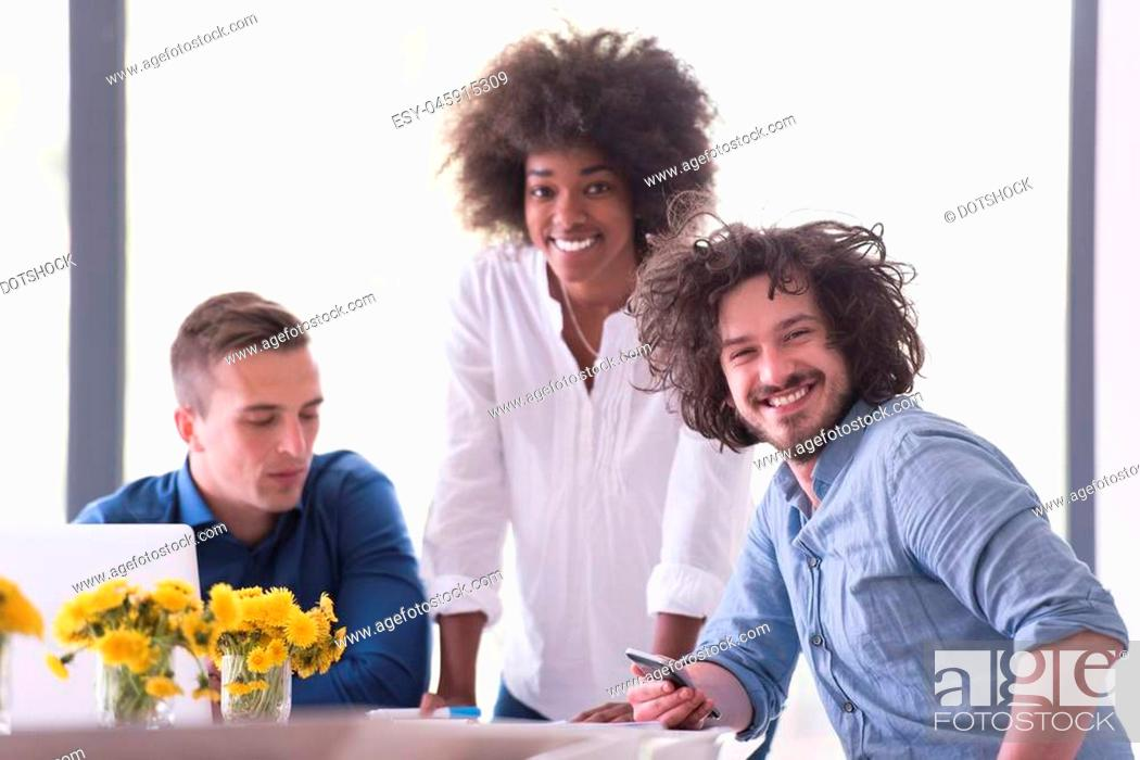Photo de stock: Multiethnic startup business team on meeting in modern bright office interior brainstorming, working on laptop and tablet computer.