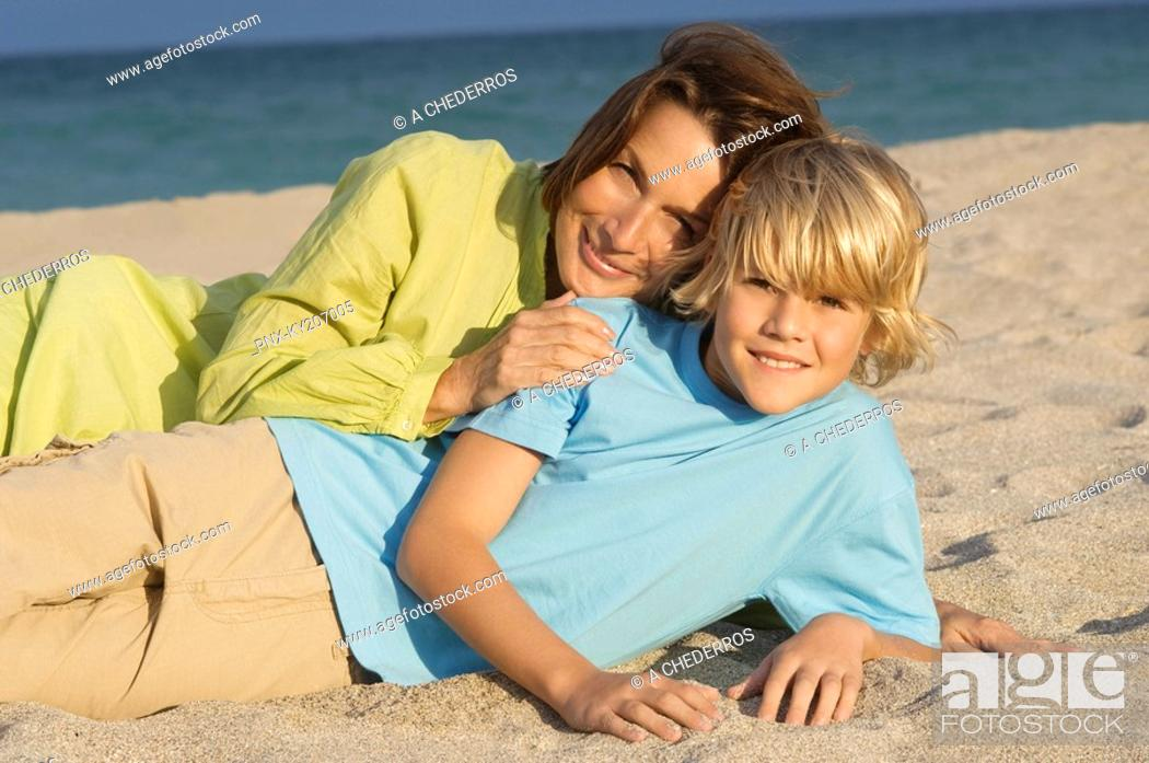 Stock Photo: Woman lying with her grandson on the beach.