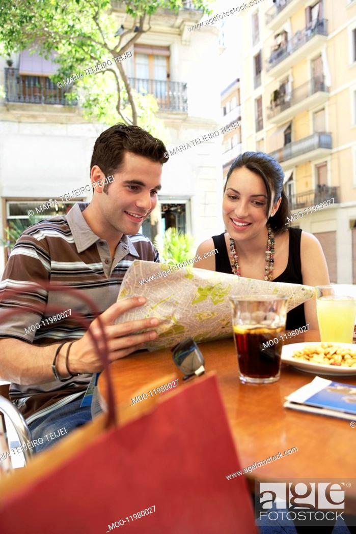 Stock Photo: Young couple at cafe reading map together portrait.