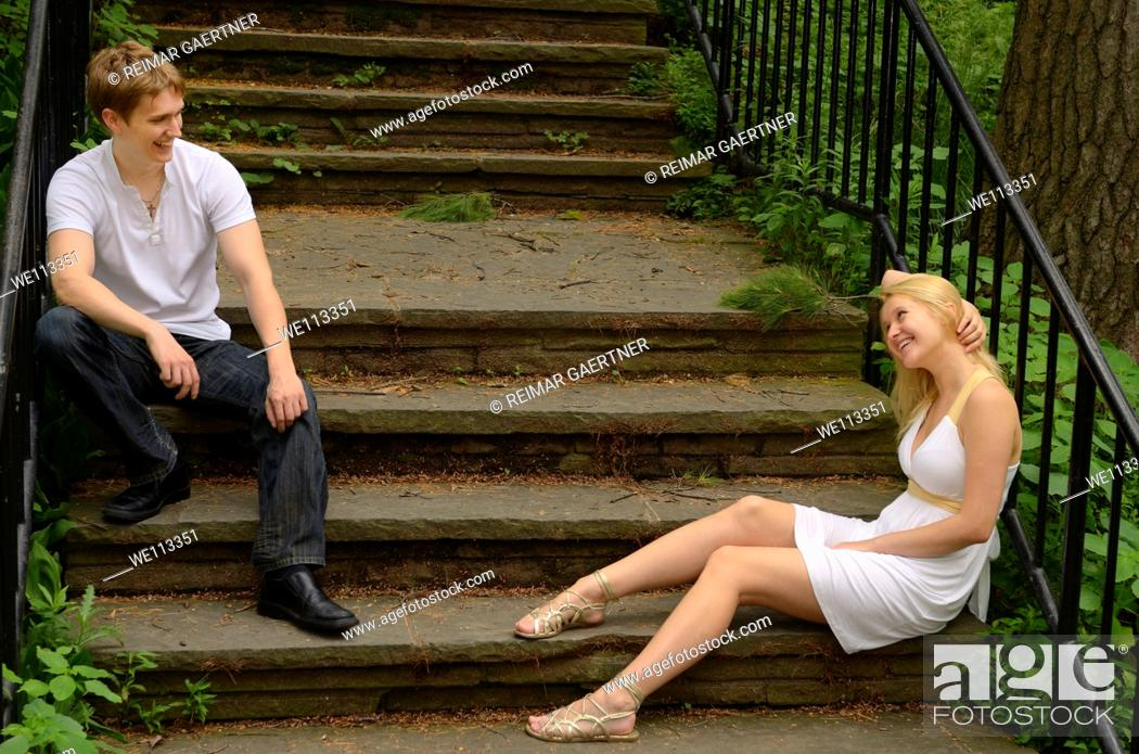 Stock Photo: Smiling couple looking at each other while sitting on stone stairs in a park.