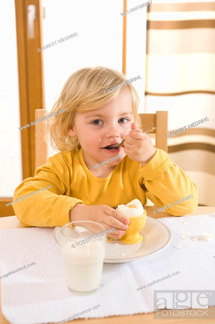 Stock Photo: Girl eating boiled egg in breakfast, eating egg.