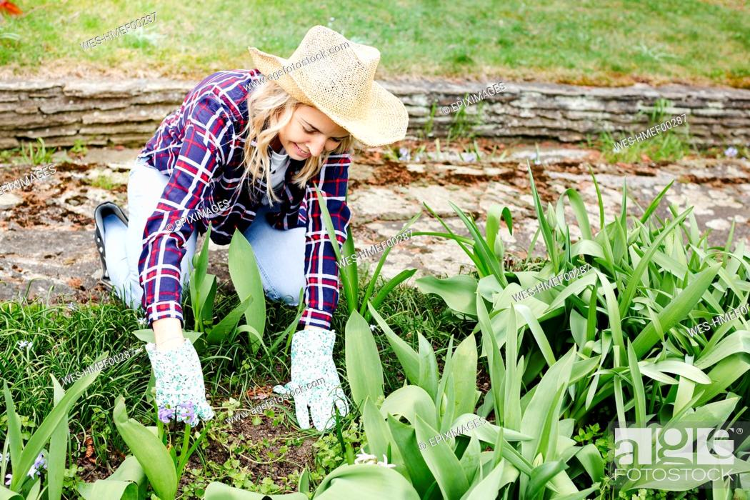 Stock Photo: Young woman with a straw hat weeding weeds.