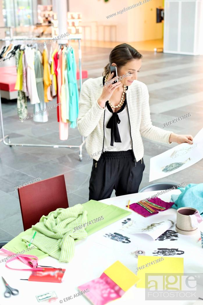 Stock Photo: Female fashion designer talking on a mobile phone in an office.