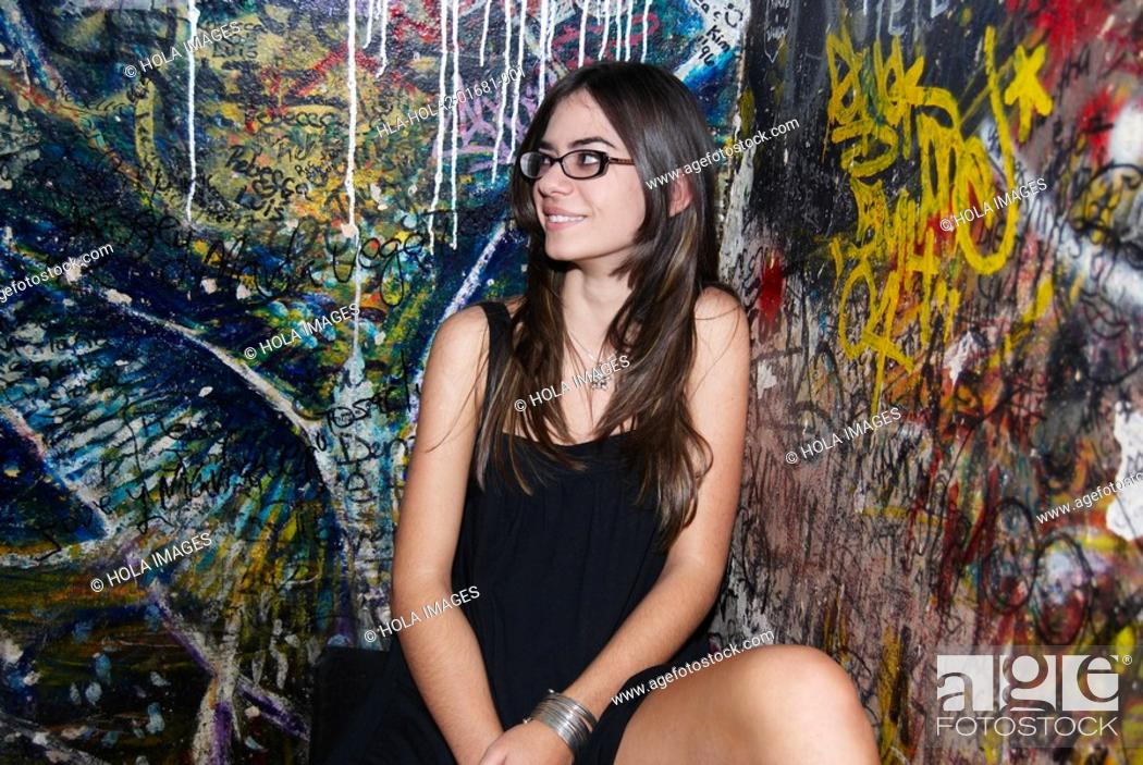 Stock Photo: Young woman sitting in front of graffiti wall.