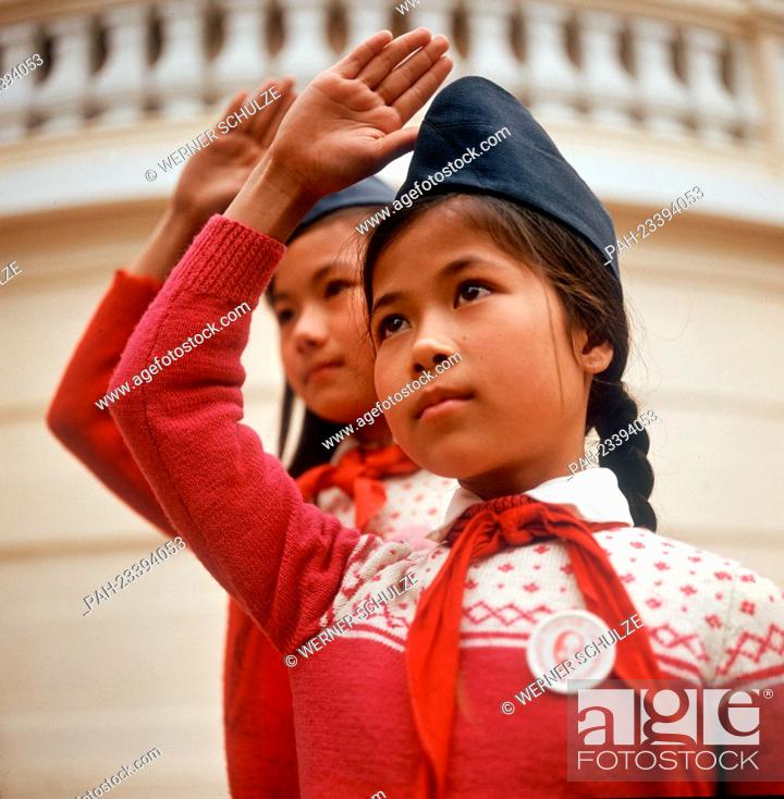 Two vietnamese girls with cap and red scarf the hand up for the stock photo two vietnamese girls with cap and red scarf the hand up for the pioneer greeting photographed in march 1973 in north vietnam m4hsunfo