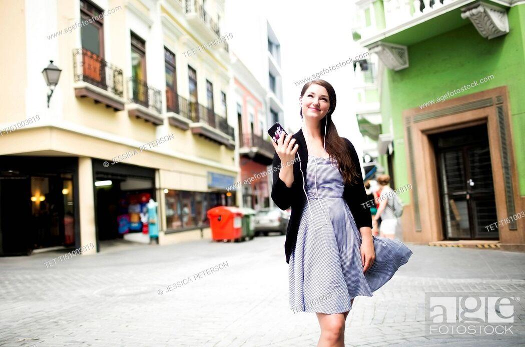 Stock Photo: Puerto Rico, San Juan, Woman standing on street and holding smart phone.