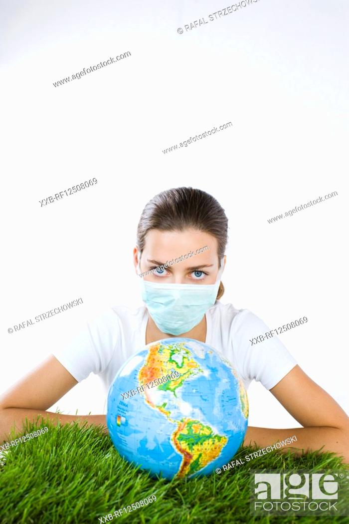 Stock Photo: young woman in mask with globe.