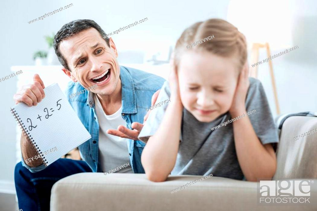 Stock Photo: Hot-tempered. Resentful dark-haired young father holding and pointing at his daughters incorrect equation and shouting at her.