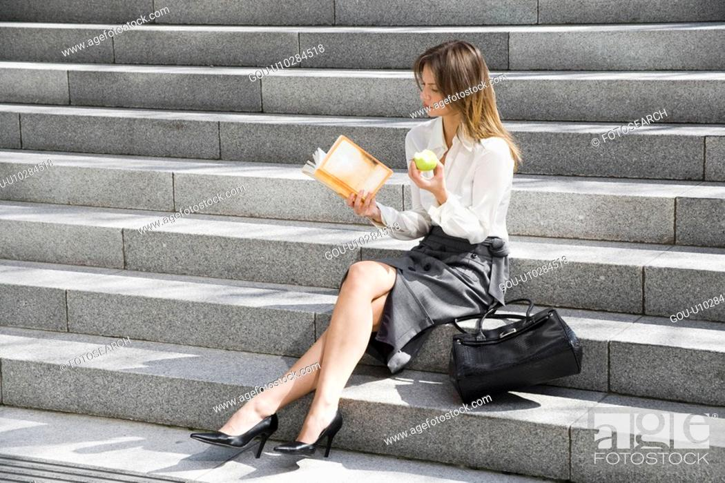 Stock Photo: Young woman reading and eating on steps.
