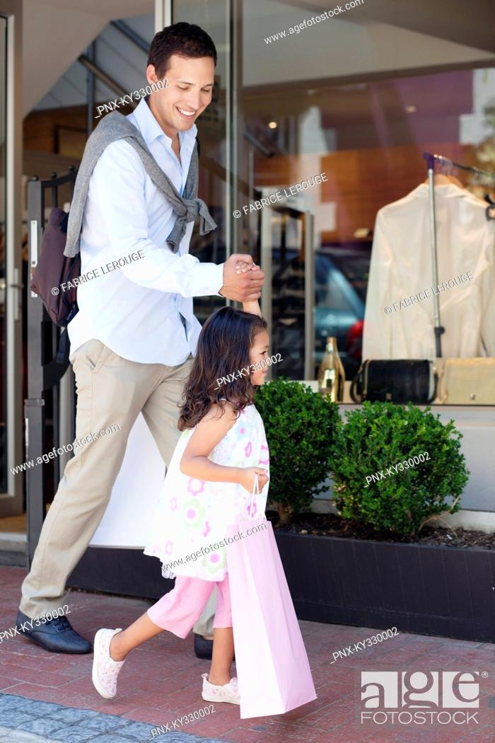 Stock Photo: Cute little girl with her father walking out of a shopping mall with shopping bags.