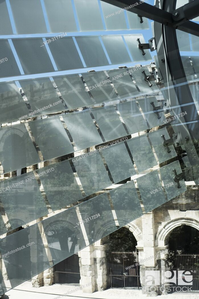 Stock Photo: Glass and stainless steel light deflectors flutter like bunting on the facade of the Roman Museum at Nimes to reveal the massive stone arches of the Roman Arena.