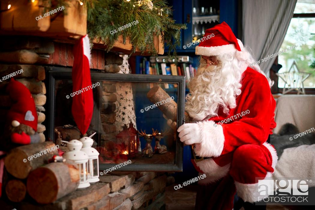 Stock Photo: Santa Claus, indoors, putting log on fire.