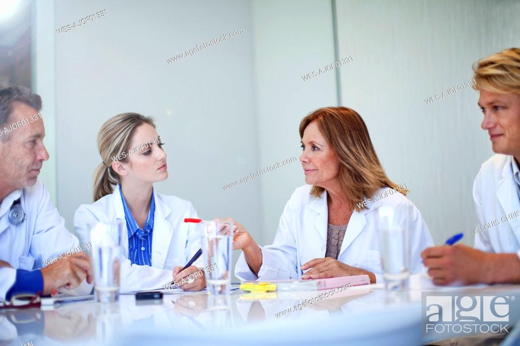 Stock Photo: Mature female doctor gesturing while discussing with healthcare workers during meeting in hospital.
