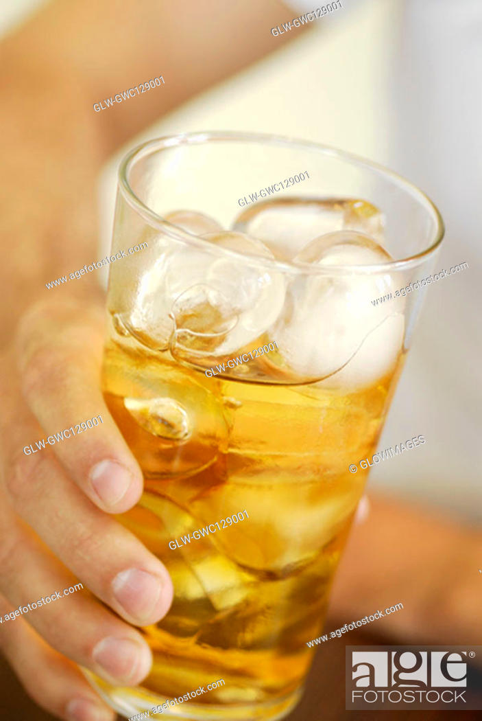 Stock Photo: Close-up of a human hand holding a glass of whiskey.