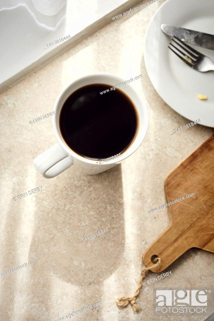Stock Photo: A woman's hand holding a white mug with coffee in a sunstreaked kitchen.