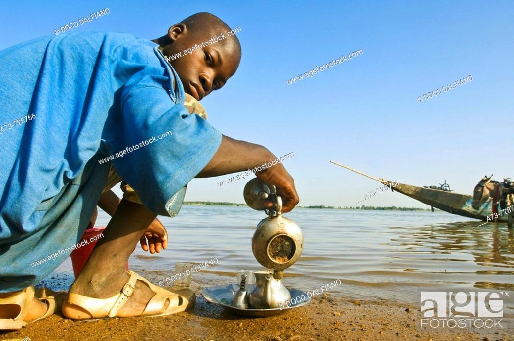 Stock Photo: Young man preparing tea by Niger River, Segou, Mali.