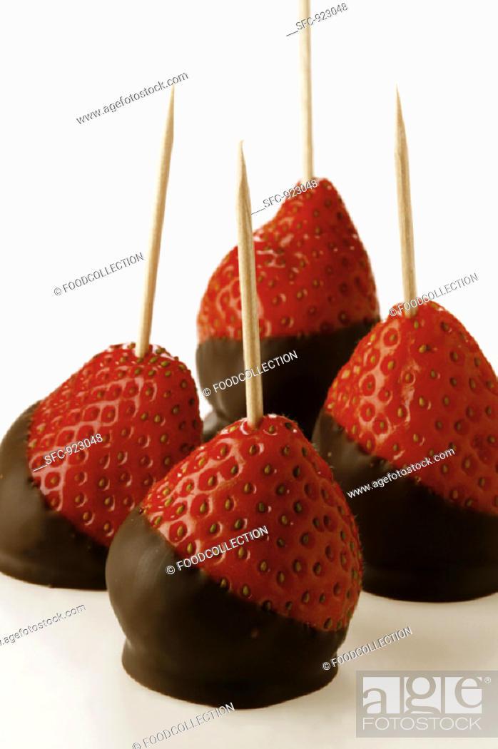 Stock Photo: Chocolate-coated strawberries on toothpicks.