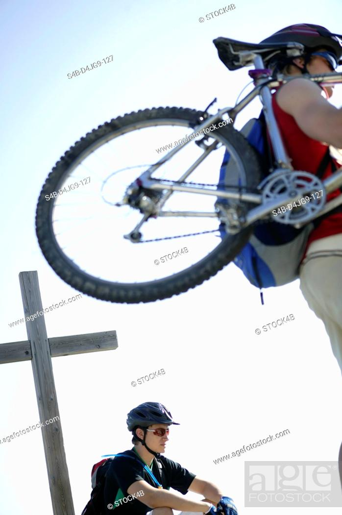 Stock Photo: Person carrying a mountainbike whereas a man in sports clothing is sitting next to a wooden cross.