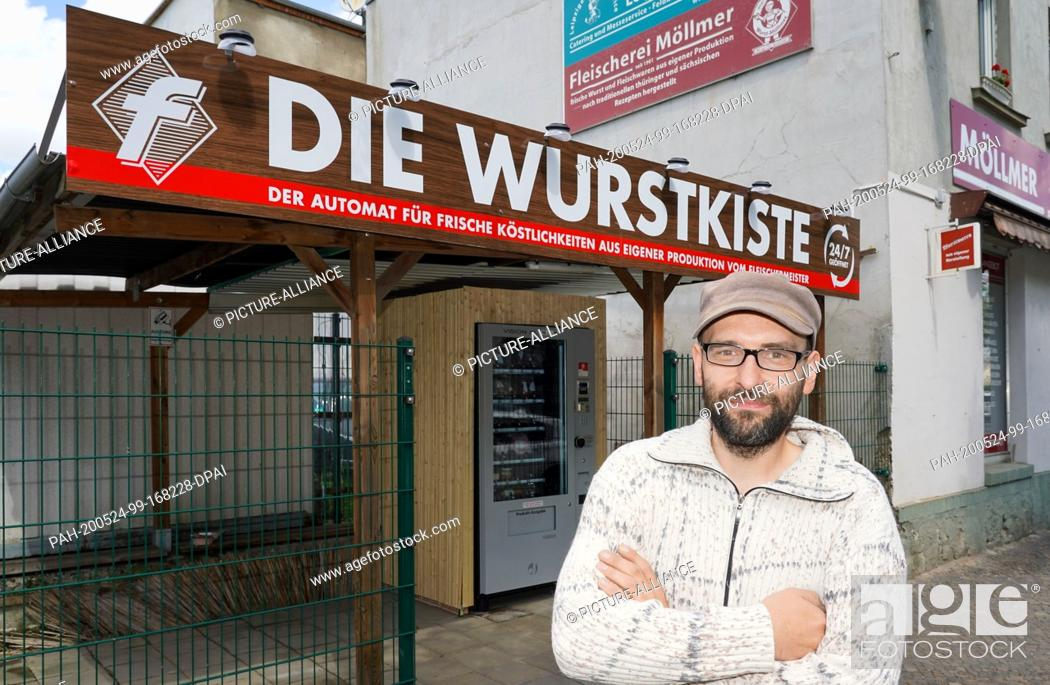 """Stock Photo: 24 May 2020, Saxony, Leipzig: Master butcher Andre Möllmer stands in front of his """"""""sausage box"""""""". The contactless purchase of meat and sausages in Corona times."""
